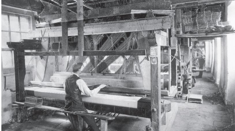 A Jacquard hand loom damask weaver at work in Coulson's, c. 1900. The workshops were long and narrow with width only for a single loom and a connecting passage way.