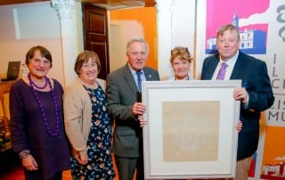 Suzanne Higgott, Rosalind Bloomfield, Councillor Brian Bloomfield MBE, Alderman Paul Porter with Deborah White, a weaver at the museum, with a framed damask napkin presented to the Wallace Collection